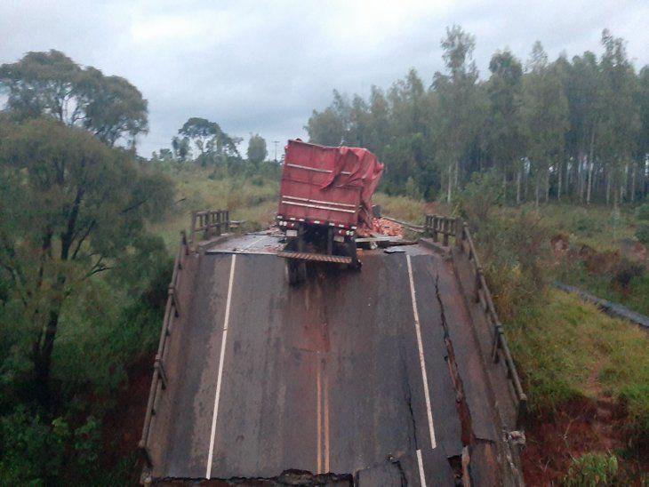 Derrumbe. La carreta del camión que transportaba materiales de construcción quedó al borde del asfalto del puente que luego cedió y fue a parar al fondo del arroyo