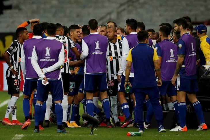 Jugadores de Atlético Mineiro chocan con sus rivales de Boca Juniors.