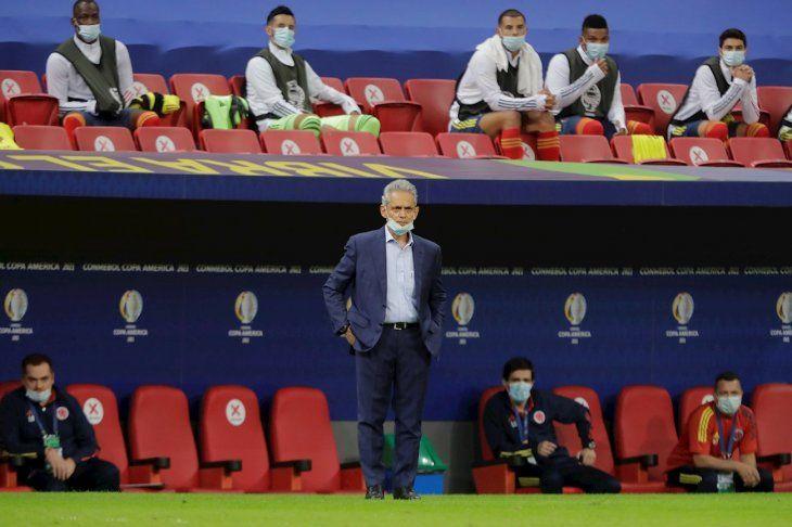 Reinaldo Rueda y jugadores suplentes de Colombia observan a su equipo.