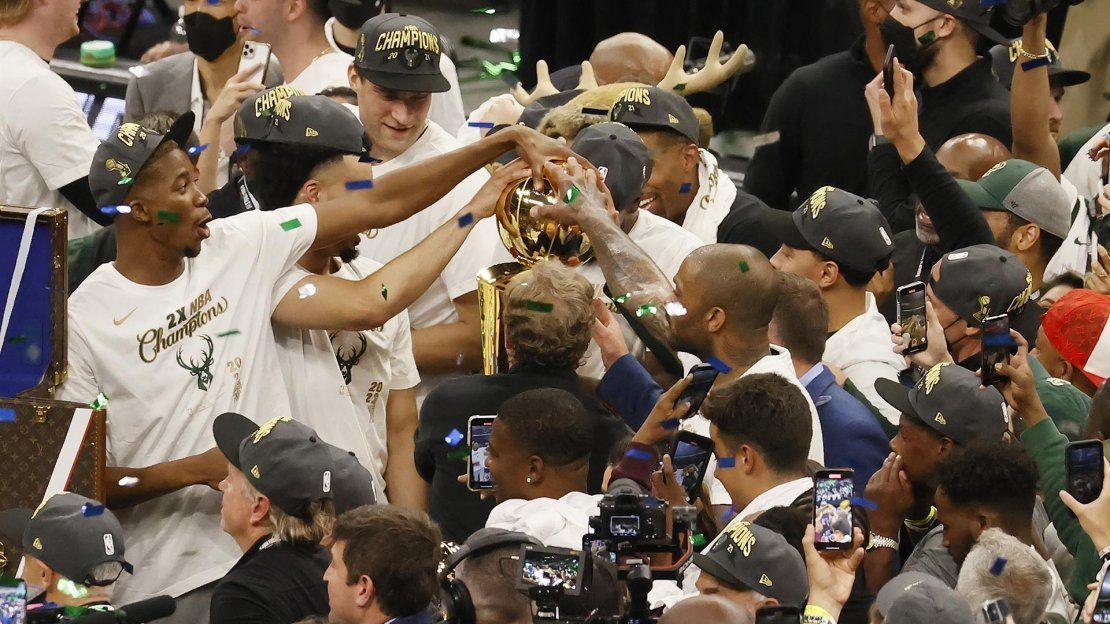 Los jugadores de los Milwaukee Bucks celebran con el trofeo Larry OBrien a la conclusión del sexto partido de la serie de baloncesto de las Finales de la NBA entre los Phoenix Suns y los Milwaukee Bucks en el Fiserv Forum de Milwaukee.