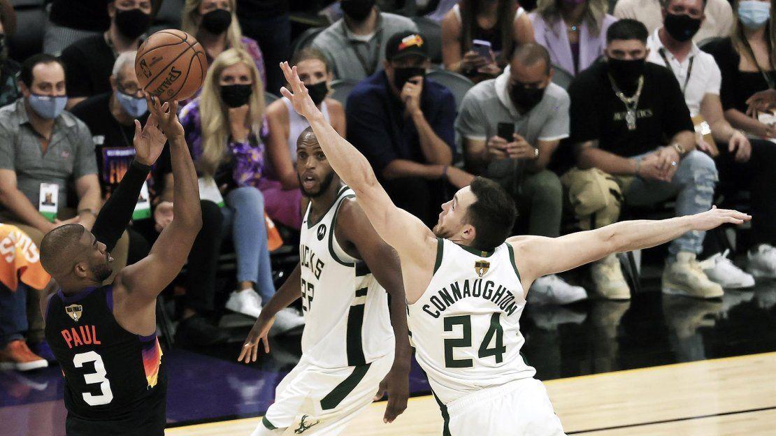 El escolta de los Suns Chris Paul (izq.) lanza sobre Pat Connaughton (dcha.) de los Bucks de Milwaukee en la segunda parte del primer partido de la serie de playoffs de las Finales de la NBA 2021 entre los Bucks de Milwaukee y los Suns de Phoenix.