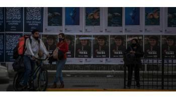 AME4967. BUENOS AIRES (ARGENTINA), 24/07/2021.- Fotografía de transeúntes en medio de paredes cubiertas con publicidad electoral, el 23 de julio de 2021, en el centro de Buenos Aires (Argentina). La campaña electoral arranca oficialmente este sábado en Argentina para las elecciones primarias del 12 septiembre, en las que los ciudadanos elegirán a los candidatos para las legislativas del 14 de noviembre, que serán los primeros comicios nacionales con Alberto Fernández como presidente. EFE/ Demian Alday Estévez