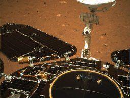 Una de las imágenes muestra la rampa de salida del Zhurong, el vehículo explorador de la misión que realiza los preparativos para abandonar la plataforma de amartizaje. La imagen, en blanco y negro, está tomada por el propio vehículo en la que será su dirección de salida, en un terreno llano y pedregoso. La fotografía también muestra los radares desplegados, mientras que la otra instantánea, de la parte trasera del Zhurong , está en color y en ella se aprecian los paneles solares y la antena, así como la anaranjada superficie de Marte.