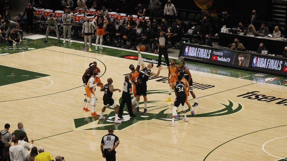 El pívot de los Milwauklee Bucks Brook López (CR) y el pívot de los Phoenix Suns Deandre Ayton (CL) se disputan el saque inicial en el primer cuarto del partido de la serie final de baloncesto de la NBA entre los Phoenix Suns y los Milwaukee Bucks.