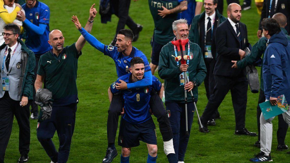 El jugador italiano Leonardo Spinazzola que se lesionó a principios del torneo celebra con su compañero Jorginho después de que Italia ganara la final de la Eurocopa 2020 entre Italia e Inglaterra en Londres