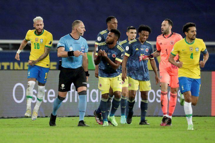 Jugadores de Colombia reclaman al árbitro Néstor Pitana.