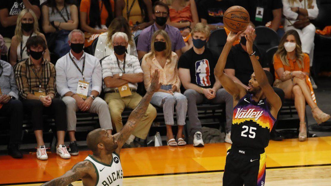 El alero de los Phoenix Suns Mikal Bridges (d) lanza sobre el alero de los Milwaukee Bucks P.J. Tucker (i) en la primera mitad del primer partido de la serie de playoffs de las Finales de la NBA 2021 entre los Milwaukee Bucks y los Phoenix Suns.