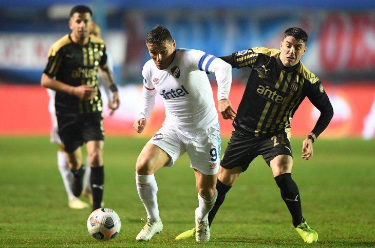 Jugadores de Nacional y Peñarol se disputan el balón.