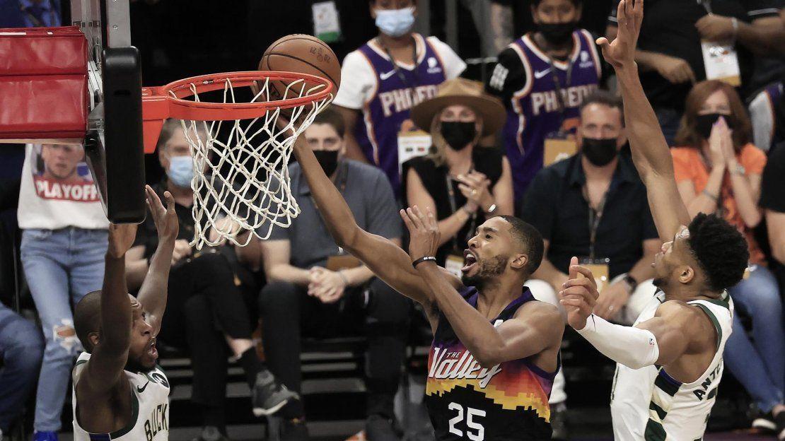 El alero de los Phoenix Suns Mikal Bridges (C) lanza entre los aleros de los Milwaukee Bucks Giannis Antetokounmpo (R) y Khris Middleton (L) en la primera mitad del primer partido de la serie de playoffs de las Finales de la NBA 2021 entre los Milwaukee Bucks y los Phoenix Suns.