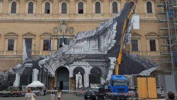 La obra simula una grieta en la fachada de este histórico edifico de Roma y muestra en blanco y negro una de sus salas más bellas, la Galería dei Carracci.