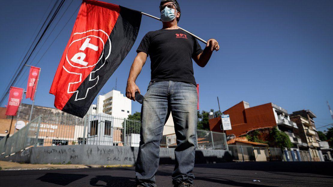 Un hombre posa con la bandera del Partido de los Trabajadores en un acto conmemorativo por el Día del Trabajador frente a la sede del Ministerio de Trabajo hoy