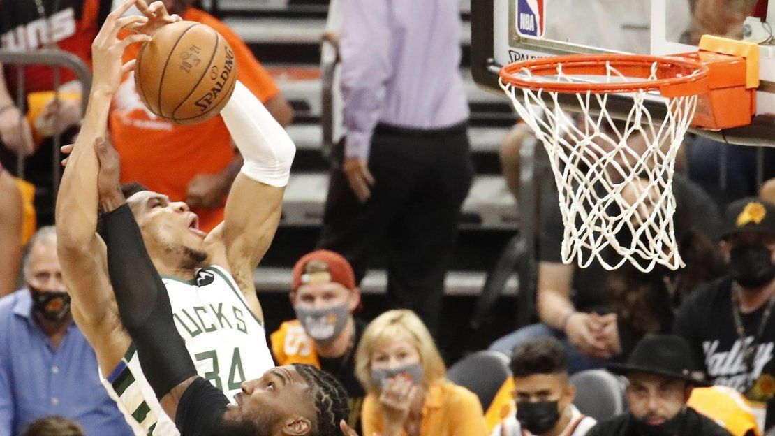 El alero de los Milwaukee Bucks Giannis Antetokounmpo (izq.) recibe una falta del alero de los Phoenix Suns Jae Crowder (dcha.) en el primer cuarto del primer partido de la serie de playoffs de las Finales de la NBA 2021 entre los Milwaukee Bucks y los Phoenix Suns en Phoenix Suns.