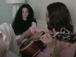 En la imagen, John Lennon toca la guitarra sentado sobre un sillón y  Ono le observa sonriente, mientras ambos cantan una versión improvisada  del himno desde una habitación del hotel Sheraton Oceanus.