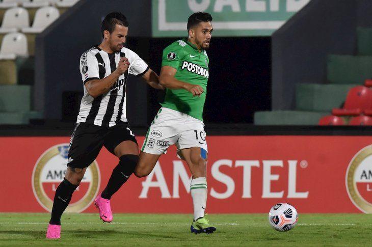 Javier Báez disputa el balón con un jugador de Atlético Nacional.