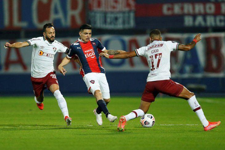 Claudio Aquino intenta pasar ante dos jugadores de Fluminense.